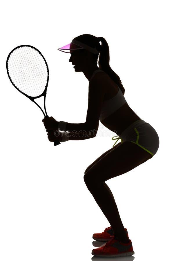 Één speler van het vrouwentennis in geïsoleerde studiosilhouet stock foto's