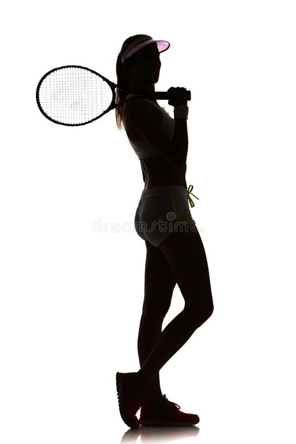 Één speler van het vrouwentennis in geïsoleerde studiosilhouet stock foto