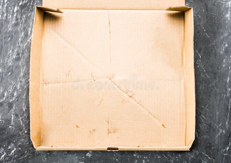 Één stuk van pizza in het vakje van de kartonpizza Hoogste mening van leeg vakje met exemplaarruimte op donker beton royalty-vrije stock afbeelding