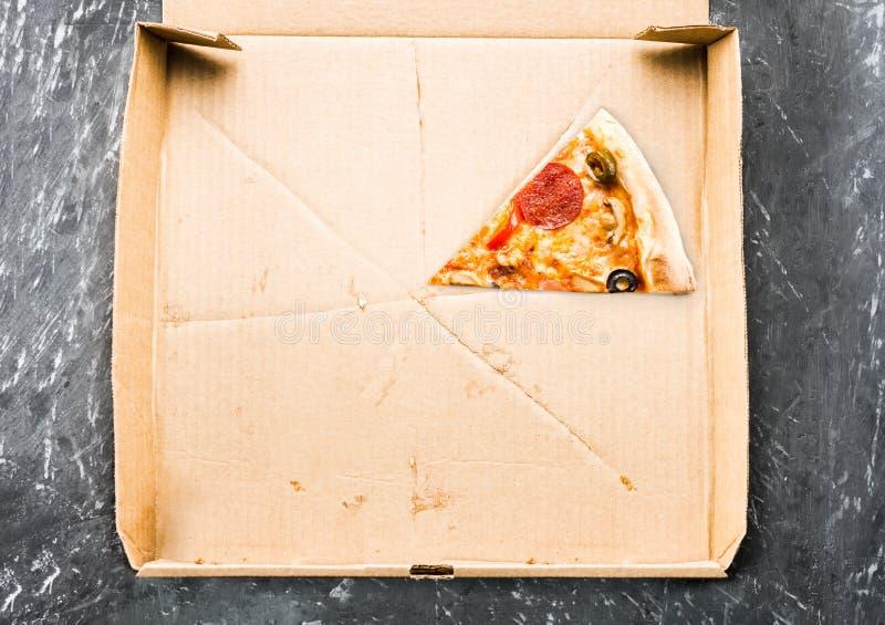 Één stuk van pizza in het vakje van de kartonpizza Hoogste mening van leeg vakje met exemplaarruimte op donker beton stock afbeelding