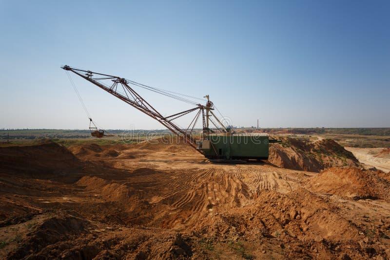 Één-toren metaal mobiele kraan op een blauwe hemelachtergrond Een industriële bewegende machine in de zandige steengroeve De ruim stock fotografie