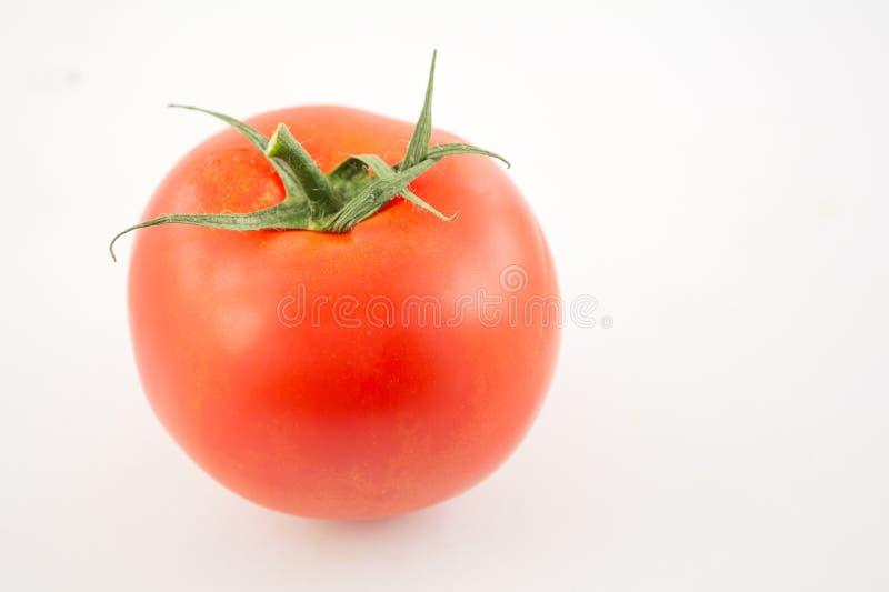 Één unpeeled, verse, rode tomaat met groene staart op wit stock afbeelding