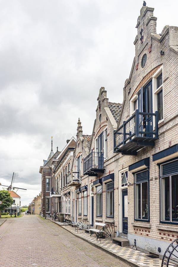 Één van de mooie straten met historische huizen en meningen van de Windmolen van Willemstad, Nederland royalty-vrije stock foto