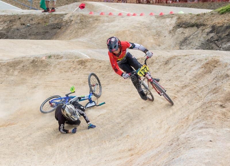 Één van het paar jonge raceauto's op de fiets valt stock foto's