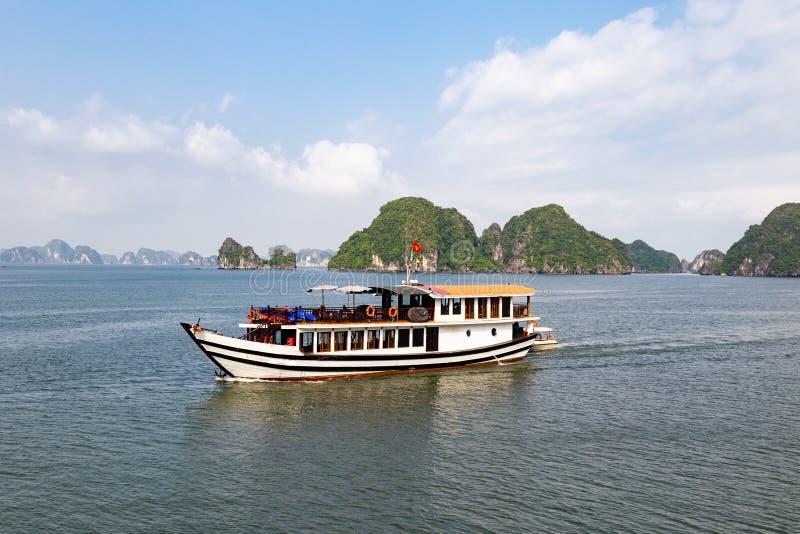 Één van velen reist boten die onder de karst vormingen in Halong-Baai, Vietnam, in de golf van Tonkin varen stock afbeelding