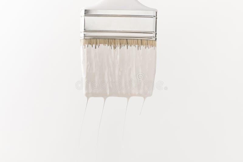 Één verfborstel in witte verf op oppervlakte stock afbeelding