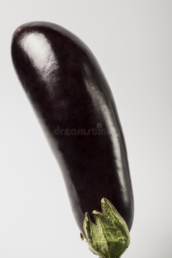 Één verse die aubergine met stam op witte achtergrond wordt geïsoleerd stock fotografie