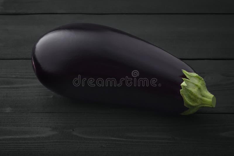 Één verse mooie aubergine donkere houten achtergrond stock fotografie