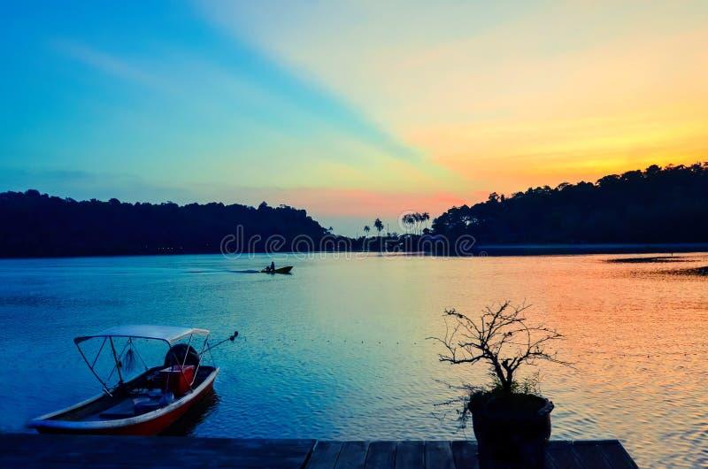 Één visser vist op de achtergrond van een kleurrijke zonsondergang dichtbij de pijler Thailand, Koh Chang stock foto's