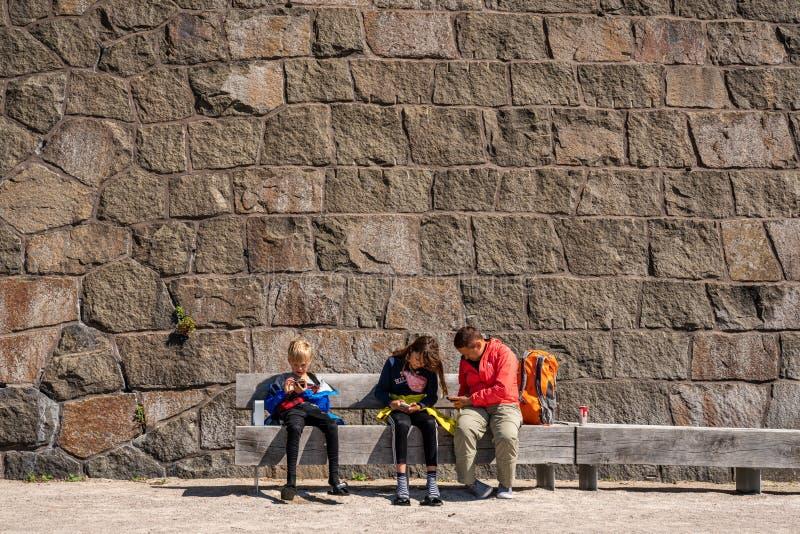Één vrouw en twee kinderen die op een bank voor een grote steenmuur bij Varbergs-Vesting zitten die hun smartphones bekijken royalty-vrije stock foto