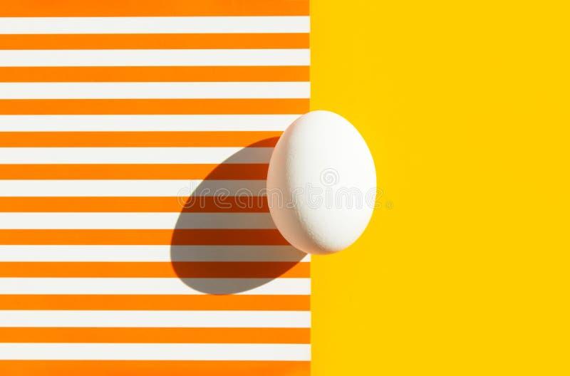 Één wit ei op duotone geeloranje en witte gestreepte achtergrond Het Concept van Pasen Harde lichte ruwe schaduw In minimalistisc royalty-vrije stock foto