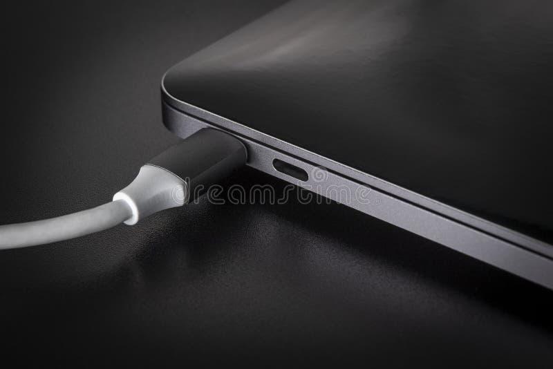 Één wit USB-type C met kabel aangesloten aan laptop stock afbeelding