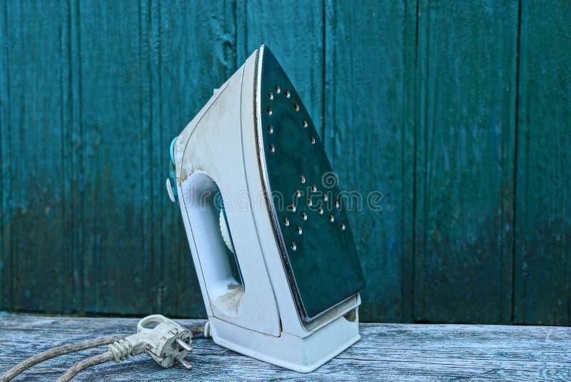 Één wit vuil elektrisch ijzer op een houten lijst tegen een groene muur stock foto