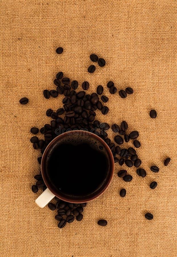 Één witte kop van verse zwarte koffiedrank op hoop van geroosterde koffiebonen op jutedekking royalty-vrije stock fotografie