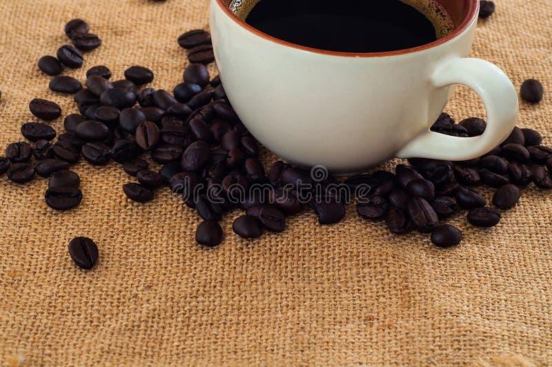 Één witte kop van verse zwarte koffiedrank op hoop van geroosterde koffiebonen op jutedekking stock foto's