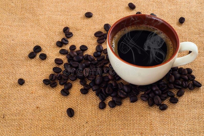 Één witte kop van verse zwarte koffiedrank op hoop van geroosterde koffiebonen op jutedekking royalty-vrije stock foto's