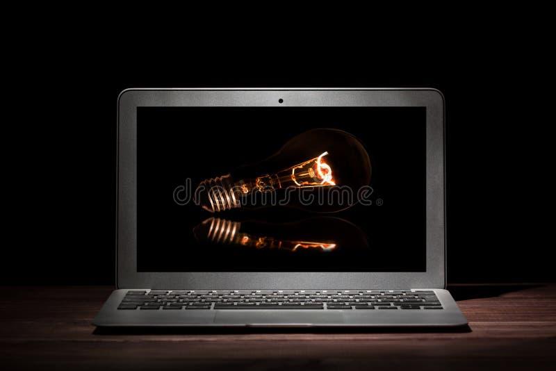 Één zilveren moderne laptop met een gloeiende gloeilamp op houten lijst in een donkere ruimte op zwarte achtergrond Het model van stock afbeeldingen