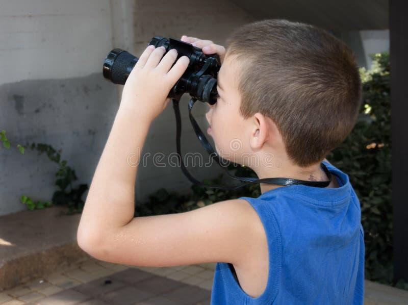 8 éénjarigenjongen die door verrekijkers kijken stock afbeeldingen