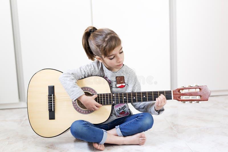 9 éénjarigenmeisje die de gitaar leren te spelen stock afbeelding