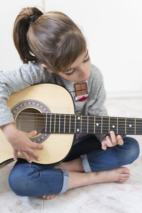 9 éénjarigenmeisje die de gitaar leren te spelen stock fotografie
