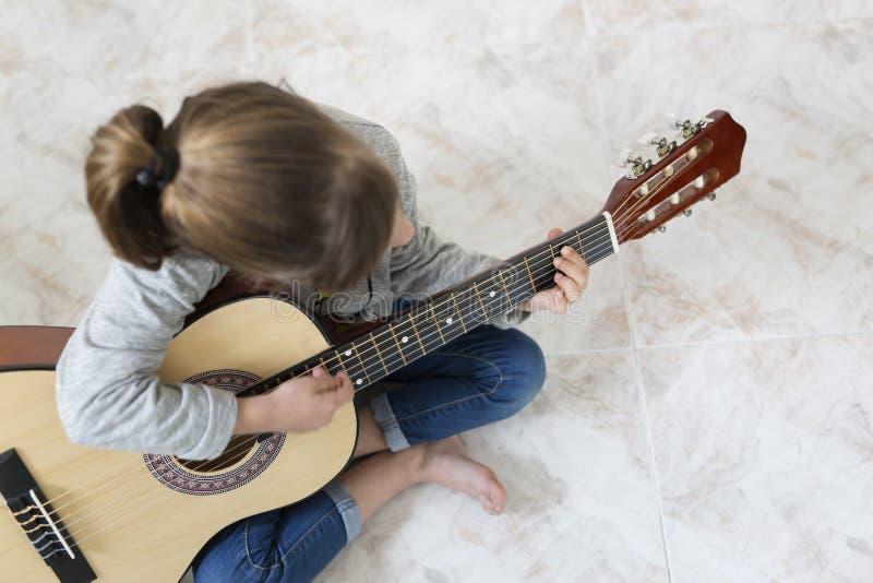 9 éénjarigenmeisje die de gitaar leren te spelen royalty-vrije stock foto