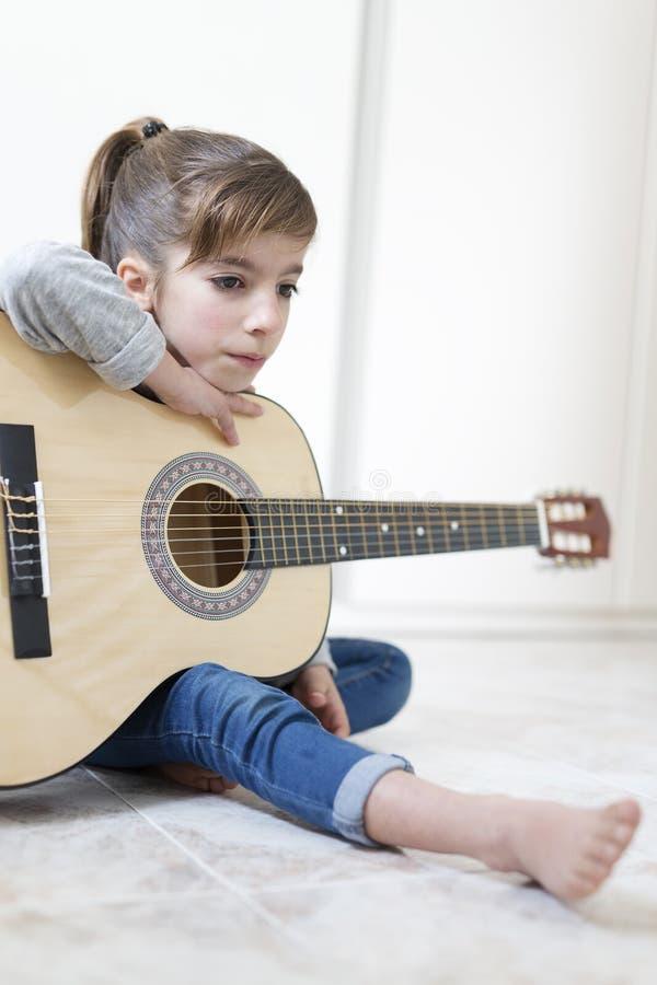 9 éénjarigenmeisje die de gitaar leren te spelen stock afbeeldingen