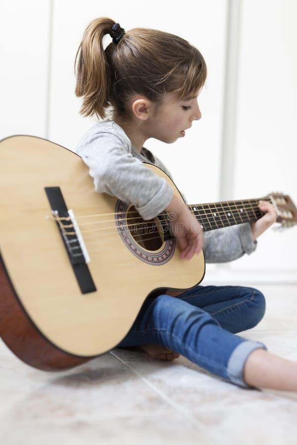 9 éénjarigenmeisje die de gitaar leren te spelen royalty-vrije stock afbeelding