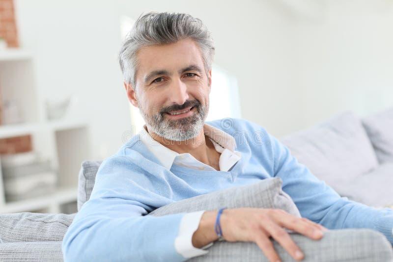 45 éénjarigenmens die thuis ontspannen stock fotografie