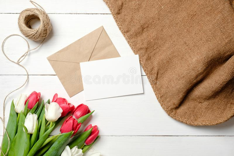 郁金香花花束,卡拉服特信封,麻线,在白色木桌上的粗麻布 葡萄酒妇女的天,母亲节贺卡, 库存图片
