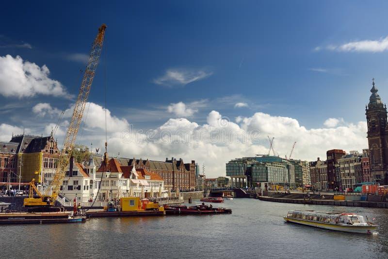 阿姆斯特丹,荷兰- 2018年9月17日:运河和阿姆斯特丹Centraal驻地的看法晴朗的夏日 图库摄影