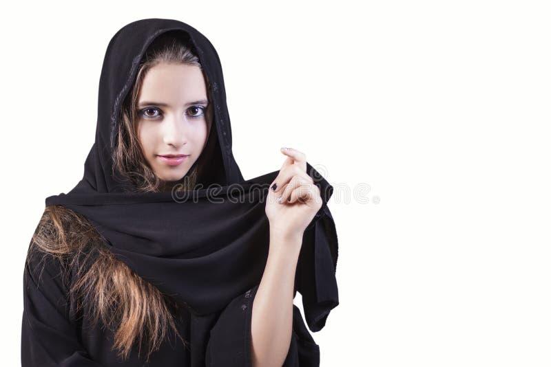 阿拉伯,回教,在白色背景的女孩特写镜头 看边的阿拉伯沙特酋长管辖区妇女面孔隔绝在白色背景 免版税库存图片