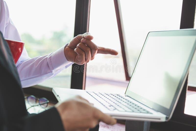 队业务会议介绍 手商人工作计划在现代办公室 在早晨光的手提电脑 免版税图库摄影