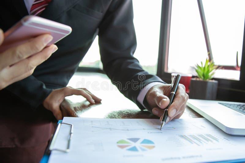 队业务会议介绍 手商人工作计划在现代办公室 手提电脑和智能手机在早晨 免版税图库摄影