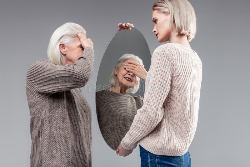闭上她的眼睛的被打动的老妇人,当看在镜子时 库存照片