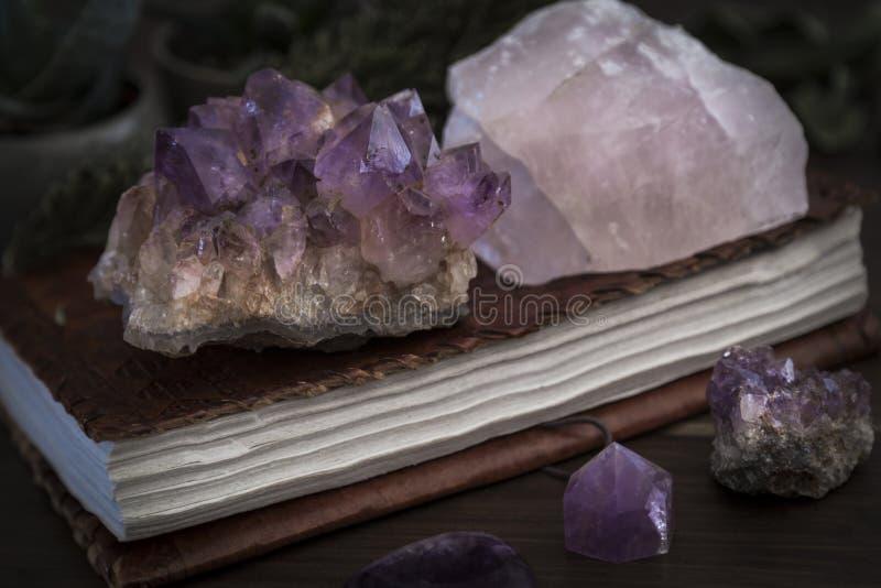 闭合的笔记本或学报与紫晶和蔷薇石英水晶在上面 库存图片