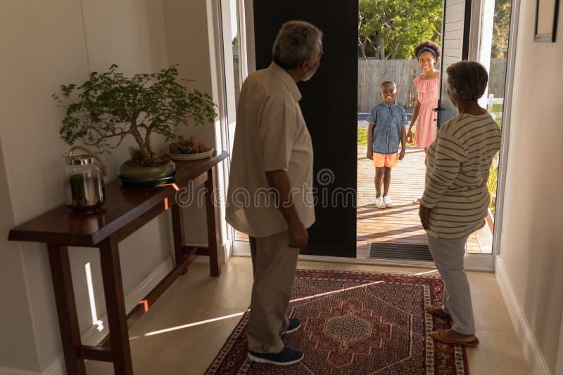 邀请的祖父母站立在门附近和他们的孙在家 免版税库存图片
