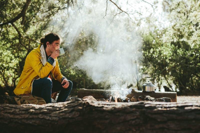 野营在森林里的人坐在篝火附近 免版税库存图片