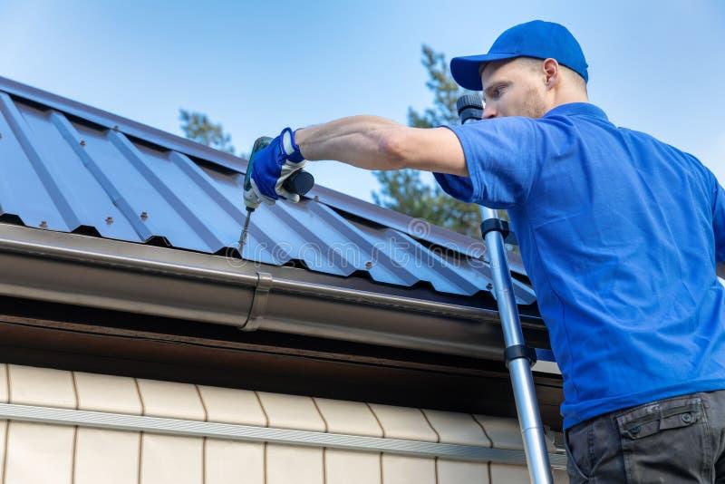 金属屋顶-工作在房子屋顶的盖屋顶的人 免版税库存图片
