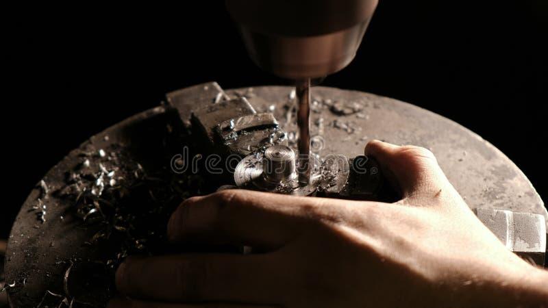 金属钻特写镜头在金属车间 做在一个铁棍的钻床一个孔 免版税库存照片