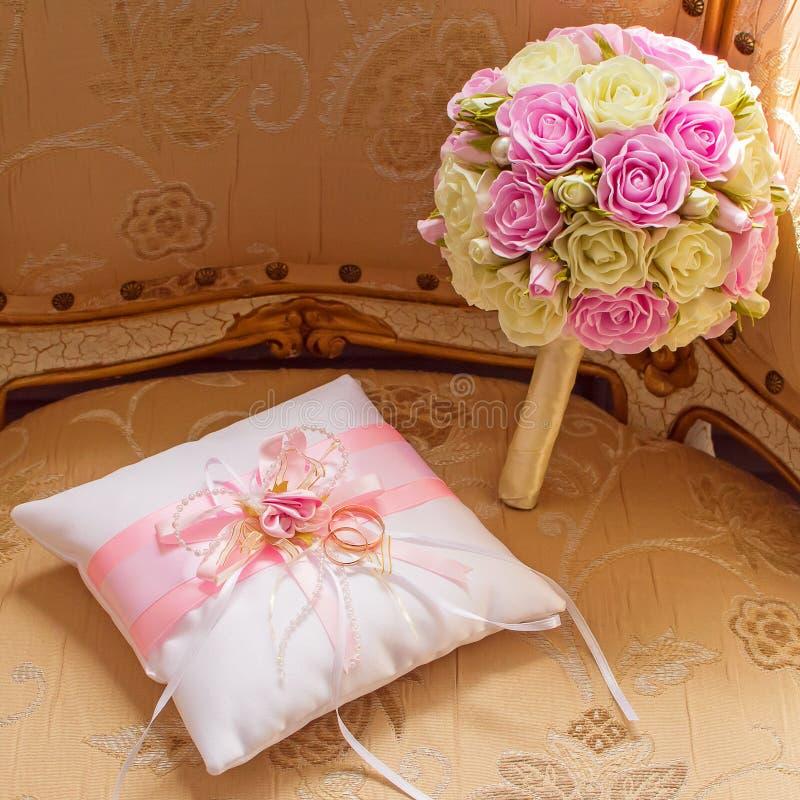 金结婚戒指和新娘的花束 桃红色和空白玫瑰 圆环的缎装饰坐垫 库存照片