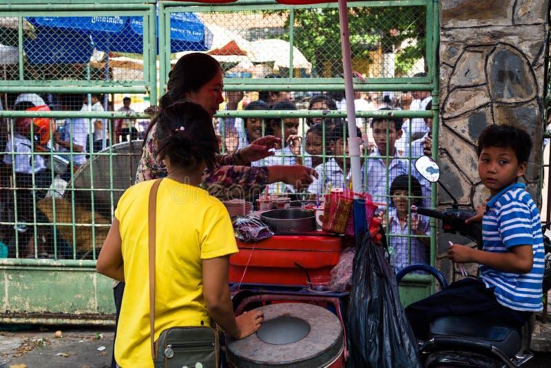金边,柬埔寨- 2018年12月8日 卖对小学生的冰淇淋供营商 免版税库存照片