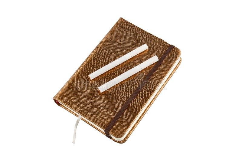金黄笔记本和香烟 背景查出的白色 免版税库存照片