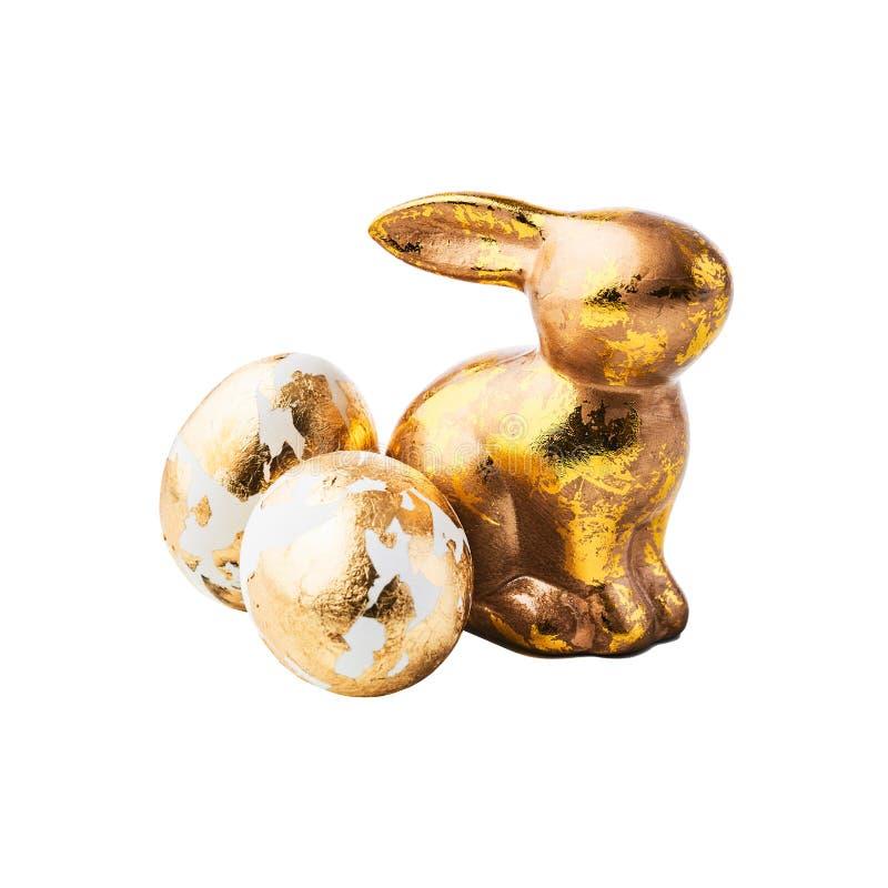 金黄用金黄箔装饰的兔子形象和鸡蛋 免版税库存图片