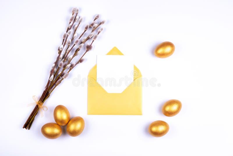 金黄色的复活节彩蛋、空插件在被打开的金黄信封和杨柳柔荑花花束在白色背景 安置文本 免版税图库摄影
