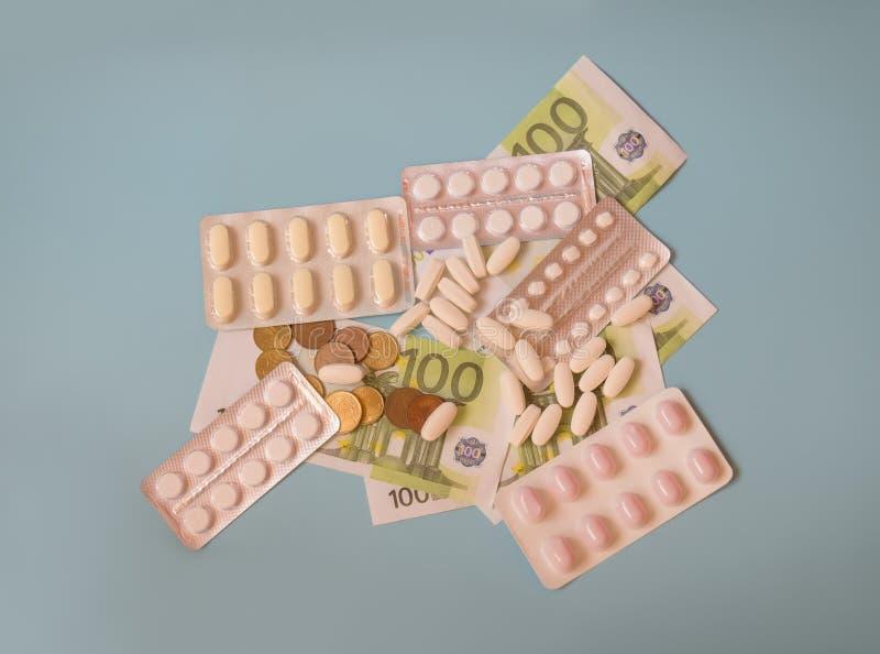 金钱、片剂和药片在蓝色背景 免版税库存图片