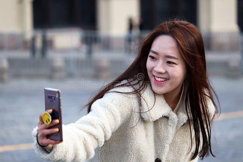 采取与智能手机的温暖的外套的俏丽的亚裔女孩一selfie 库存照片