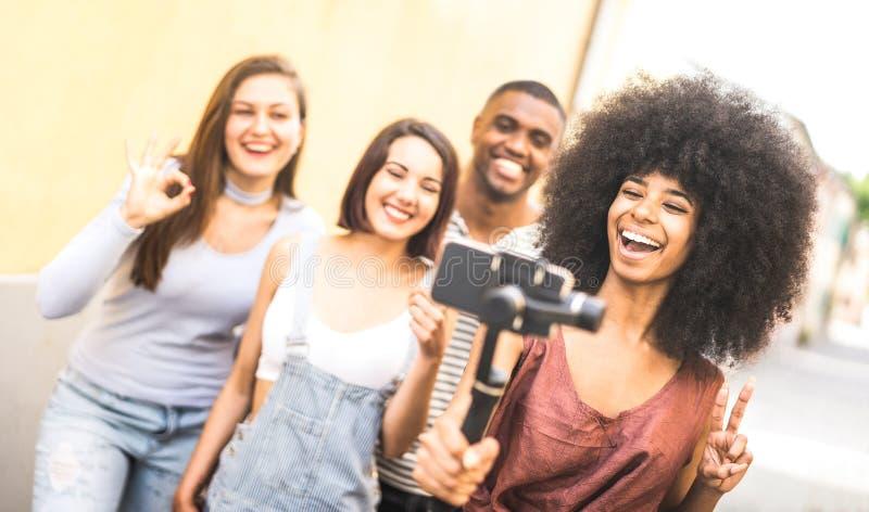 采取与被稳定的手机-年轻朋友的千福年的人民录影selfie获得在新的技术趋向的乐趣-青年时期和 免版税图库摄影