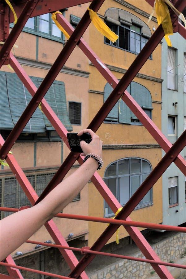 采取在一座金属步行桥的妇女的手一selfie在希罗纳,西班牙 免版税库存图片