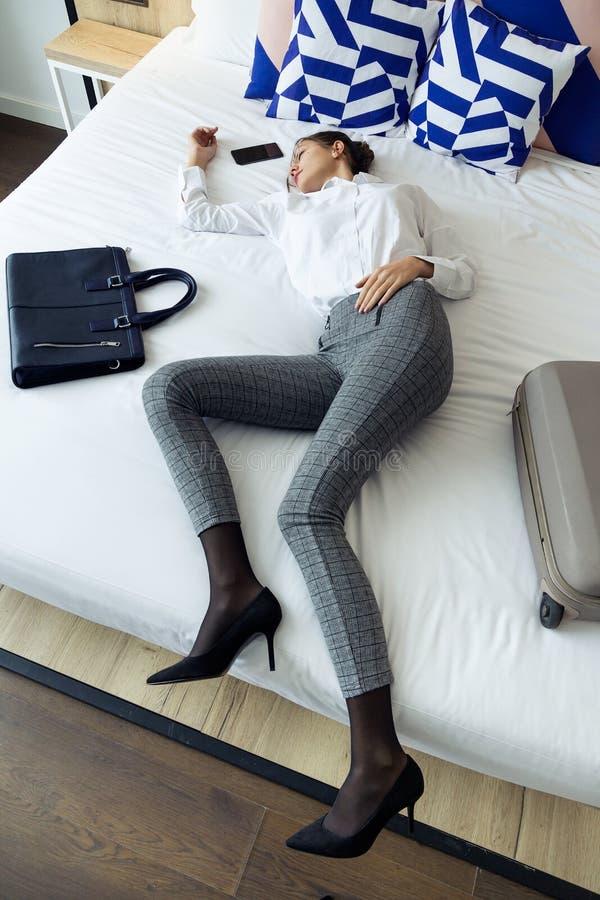 采取其余在床上的努力工作日的衣服的被用尽的年轻女实业家在酒店房间 库存照片