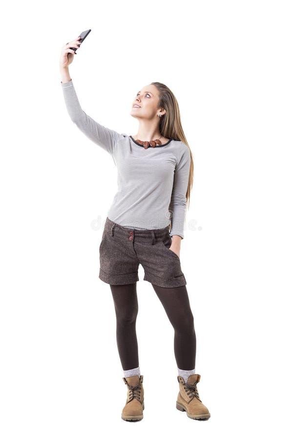 采取和摆在为与智能手机的selfie画象的凉快的质朴的轻松的行家女孩 库存照片